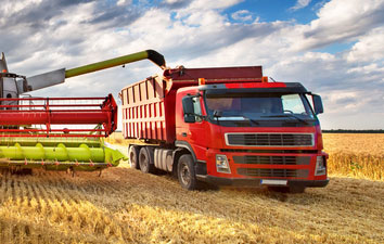 farm equipment pumping grain into a truck in the field