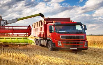 farm equipment pumping grain into a truck in the field