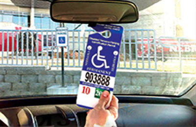 handicap permit hanging on rear-view mirror inside vehicle