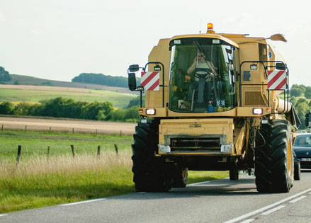 large yellow farm equpiment driving on road