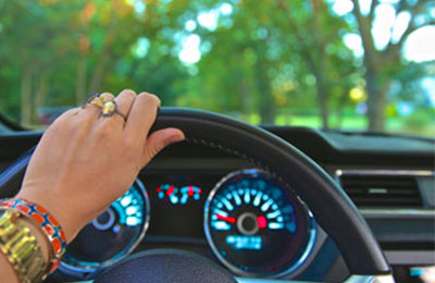 hand on steering wheel driving vehicle