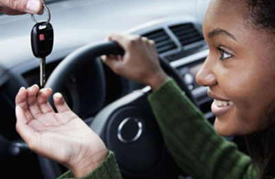 teen girl being handed the keys to the while sitting behind the wheel