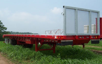 red flatbed trailer parked in grass field