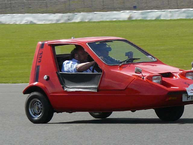 red 3-wheeled autocycle on road