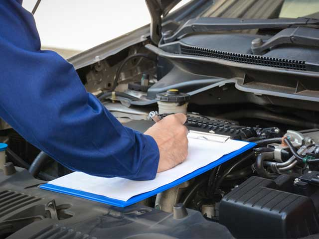 person filling out checklist on open engine vehicle