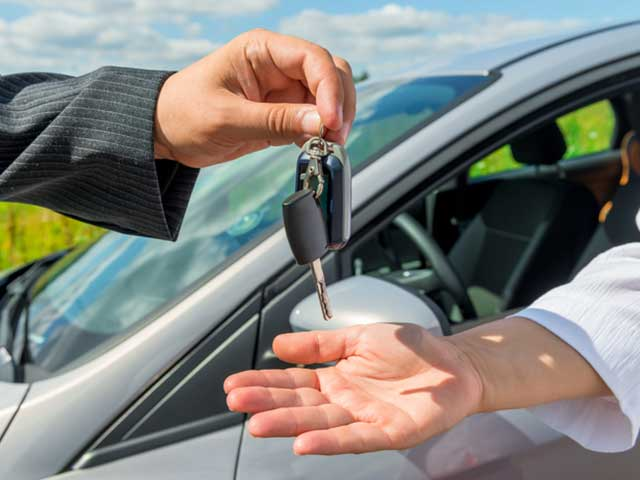 handing over new car keys to man sitting in vehicle