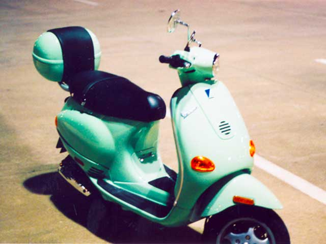 front of green vespa in parking lot