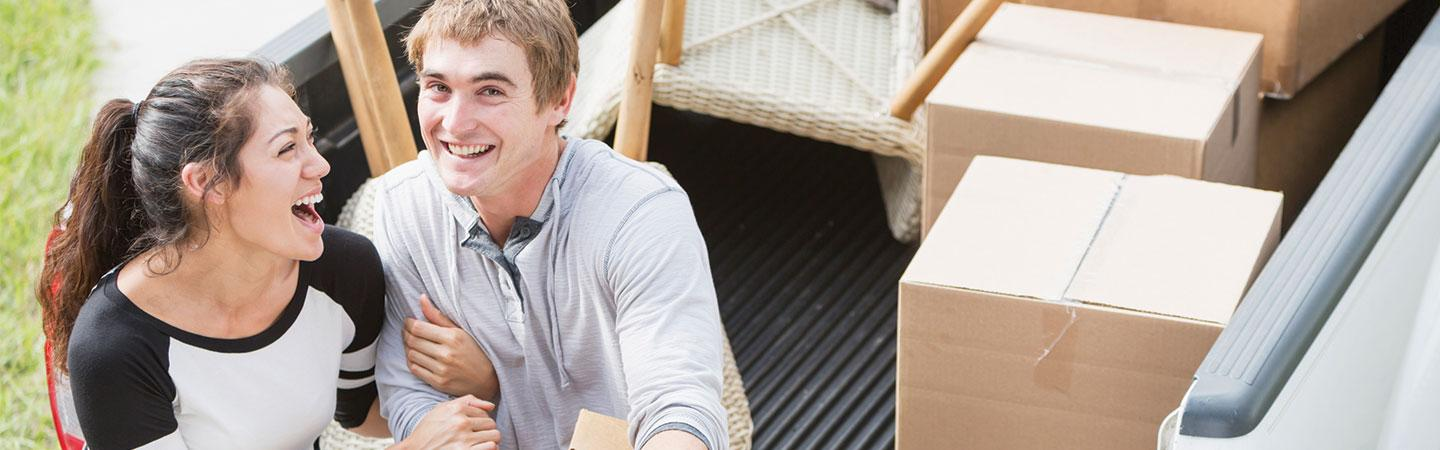 young couple laughing wil sitting on pickup bed with boxes and a chair in it