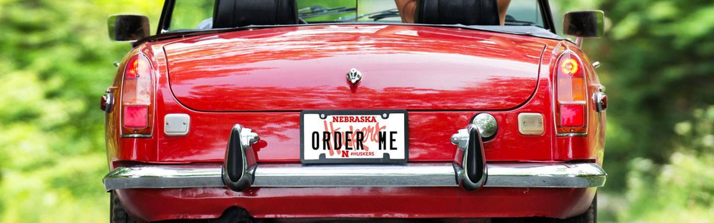 "back of shiny red car with a custom Husker license plate that says ""ORDER ME"""